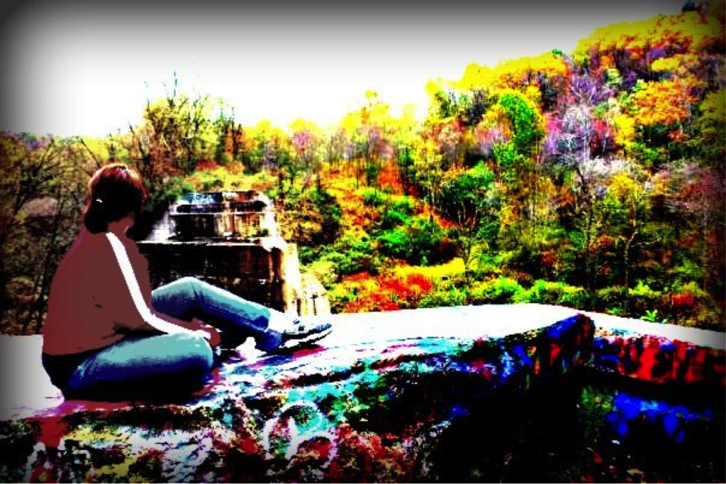 Carly Masiroff with back to camera looking out over a waterfall landscape in distorted color