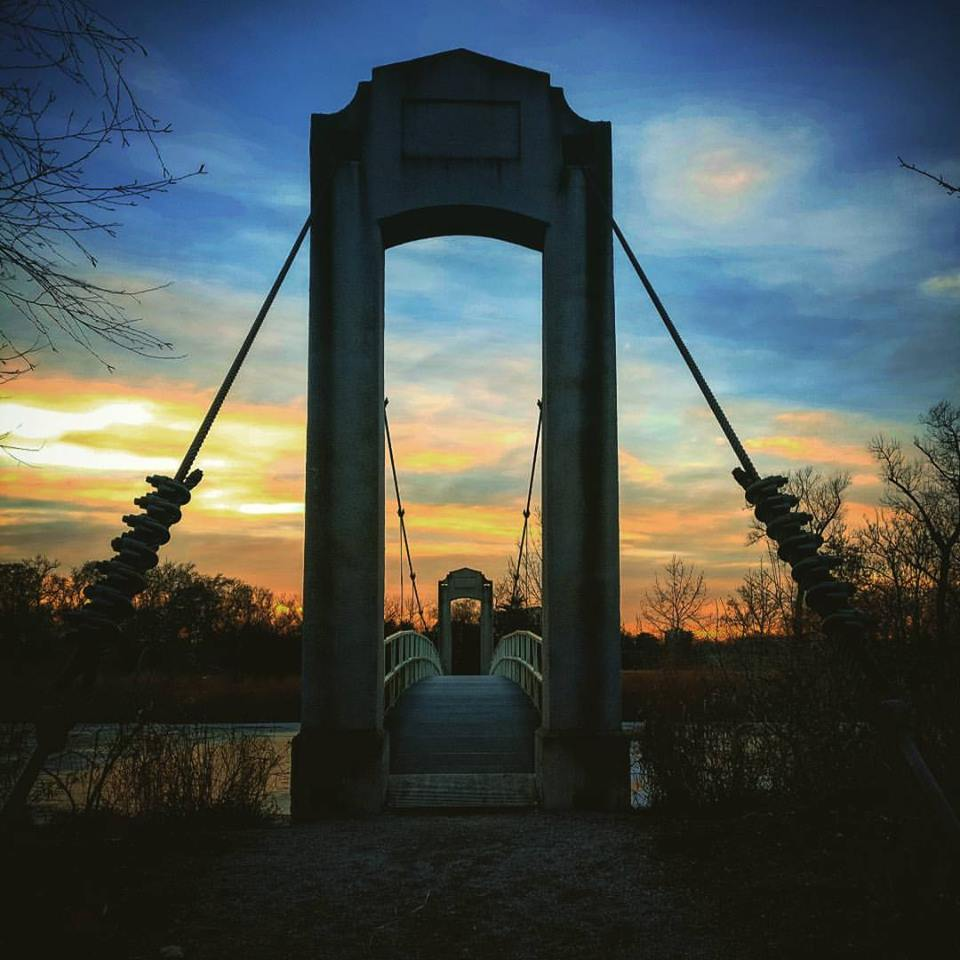 Picture of a pedestrian bridge with the sunset behind it.