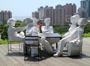 Six figures are sitting around a table, engaging in dialogue.