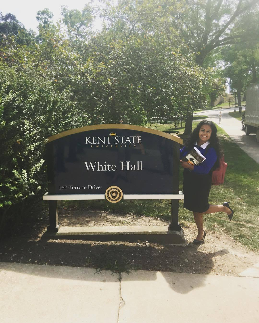 Author is posing next to building sign on Kent State University's campus.