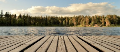Wooden dock in foreground of picture overlooking blue water and trees
