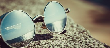 close up photo of sunglasses on a concrete wall